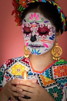Une jeune femme déguisée en catrina avec un costume mexicain, posant avec un fond uni et une bougie
