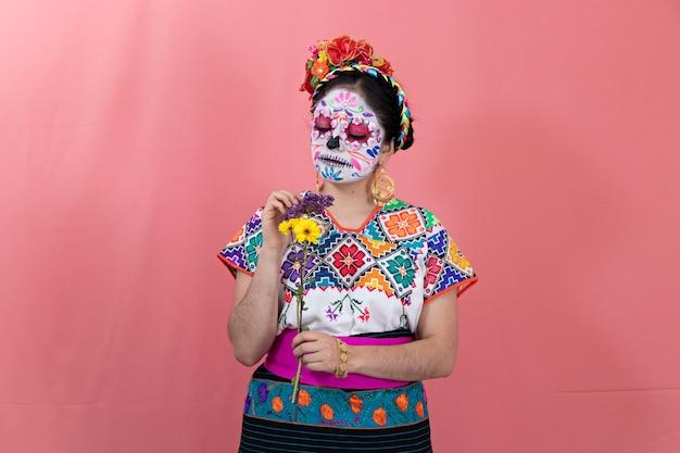 Une jeune femme déguisée en catrina avec un costume mexicain, posant avec un fond uni et des fleurs