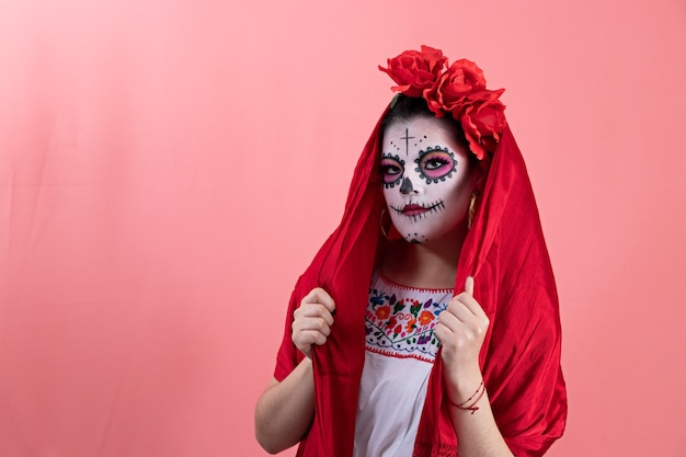 Une jeune femme déguisée en catrina avec un costume mexicain, posant avec un fond uni