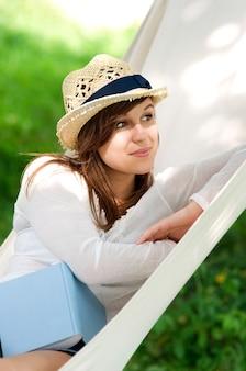 Jeune femme, délassant, dans, a, hamac, à, livre