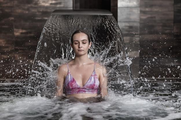 Jeune femme, délassant, sous, courant eau, dans, piscine