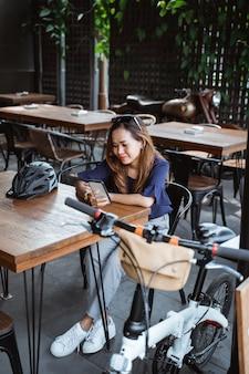 Jeune femme, délassant, utilisation, smartphone, et, coupure, à, café, après, cyclisme