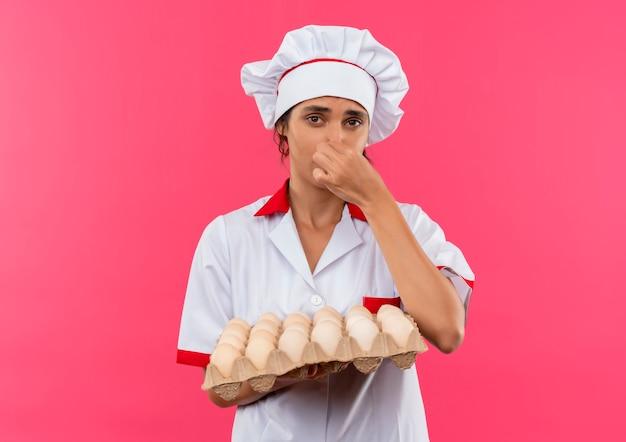 Jeune femme délicate cuisinier portant l'uniforme de chef holding lot d'oeufs et nez fermé sur un mur rose isolé avec copie espace