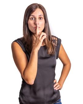 Jeune femme demandant le silence sur fond blanc