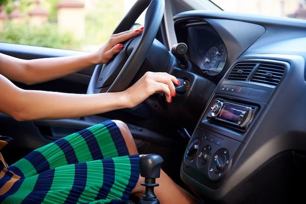 Jeune femme démarre le moteur de la voiture.