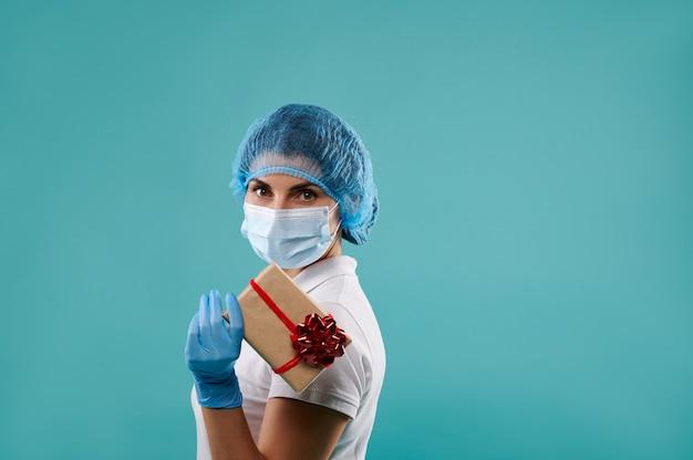 Jeune femme dentiste dans un chapeau et un masque détient un cadeau de noël.