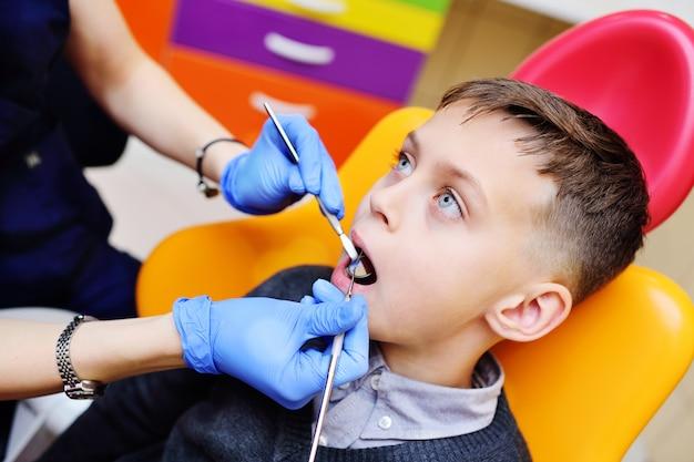 Jeune femme dentiste examine les dents d'un petit garçon assis dans le fauteuil dentaire.