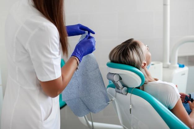 Jeune femme dentiste et patiente dans le fauteuil dentaire au bureau.