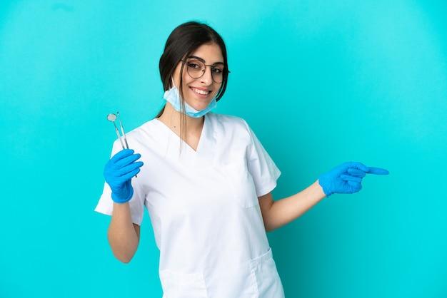 Jeune femme dentiste de race blanche tenant des outils isolés sur fond bleu, pointant le doigt sur le côté