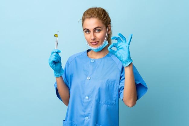 Jeune femme dentiste tenant des outils sur un mur bleu isolé montrant un signe ok avec les doigts