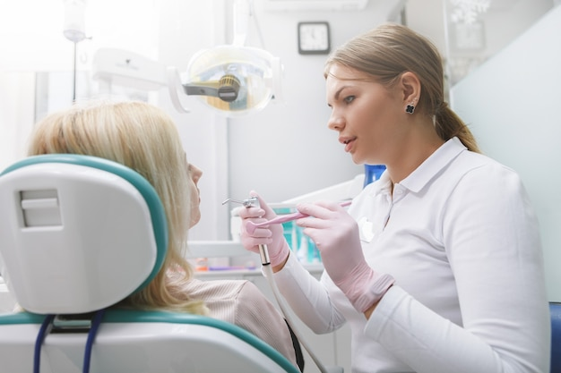 Jeune femme dentiste travaillant dans sa clinique, parlant à son patient
