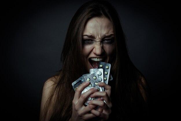 Jeune femme déprimée à l'aide de pilules