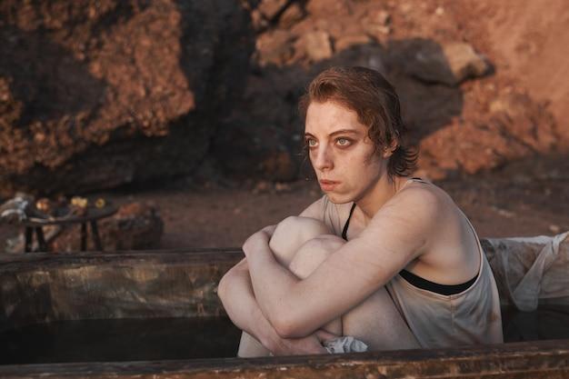 Jeune femme déprimée assise dans un bain sale regardant le coucher du soleil et pensant à quelque chose à l'extérieur