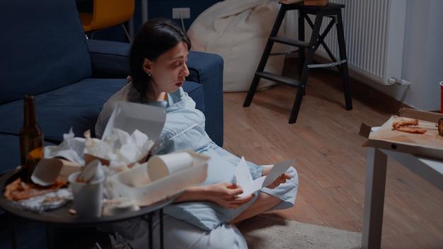 Jeune femme déprimée, désespérée, frustrée, pleurant, lisant une lettre de notification de dette mauvaise fi...