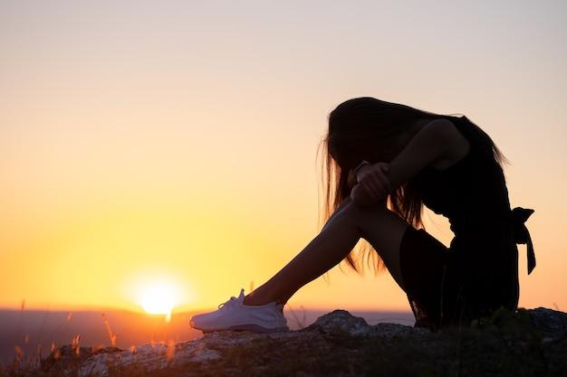 Jeune femme déprimée en robe d'été courte noire assise sur une colline de montagne pensant à l'extérieur au coucher du soleil. femme solitaire contemplant dans une chaude soirée dans la nature.