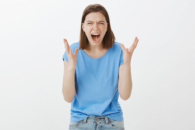 Jeune femme déprimée et stressée hurlant, se sentant fatiguée et haineuse, hurlant