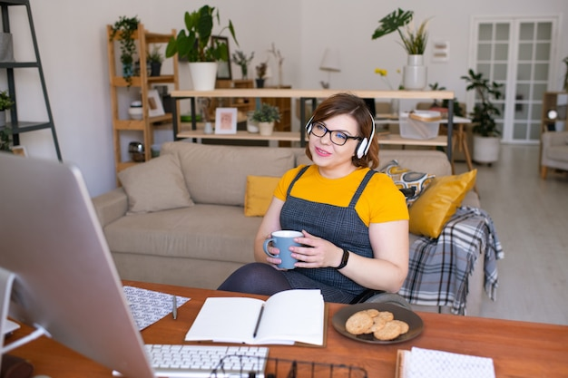 Jeune femme désactiver dans les écouteurs assis sur un fauteuil roulant devant un écran d'ordinateur tout en ayant une leçon en ligne dans le salon