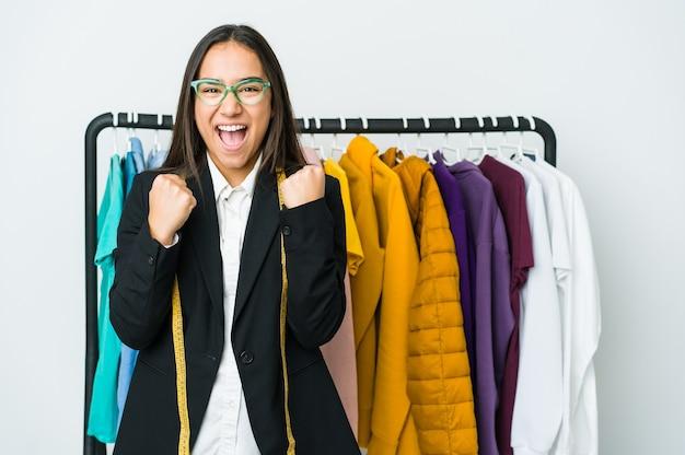 Jeune femme de designer asiatique isolée sur un mur blanc applaudissant insouciant et excité