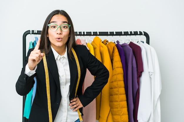 Jeune femme de designer asiatique isolée sur un mur blanc ayant une idée, un concept d'inspiration