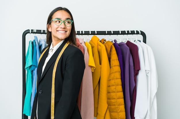 Jeune femme de designer asiatique isolée sur un mur blanc regarde de côté souriant, gai et agréable
