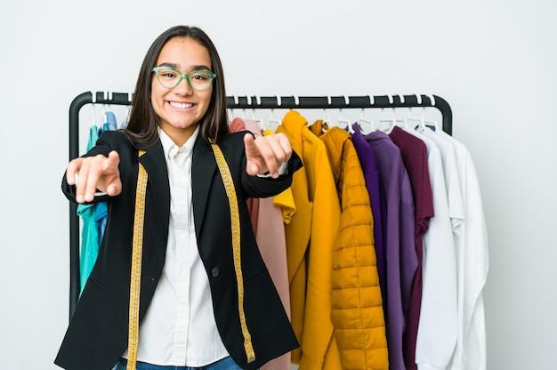 Jeune femme de designer asiatique isolée sur mur blanc sourires joyeux pointant vers l'avant