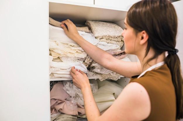 Jeune femme designer choisir le tissu de l'étagère