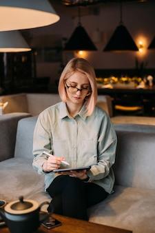 Jeune femme de designer créatif tenant un stylet dessin sur tablette numérique dans un café moderne