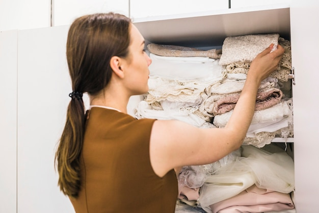 Jeune femme designer regardant le tissu en rayon