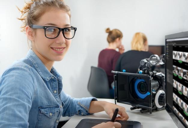Jeune femme designer utilisant une tablette graphique pour le montage vidéo