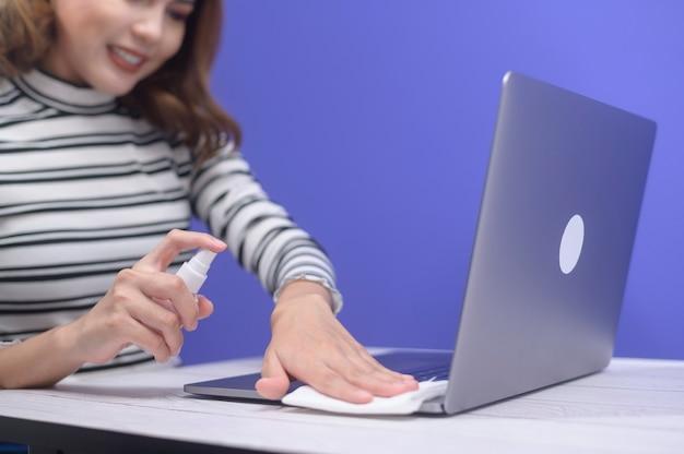 Jeune femme désinfectant le spray d'alcool avec ordinateur, concept de protection covid-19.