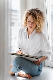 Jeune femme dessin à la maison près de la fenêtre