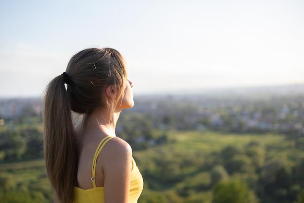 Jeune femme détendue debout dans un champ vert en regardant le coucher de soleil dans la nature du soir.