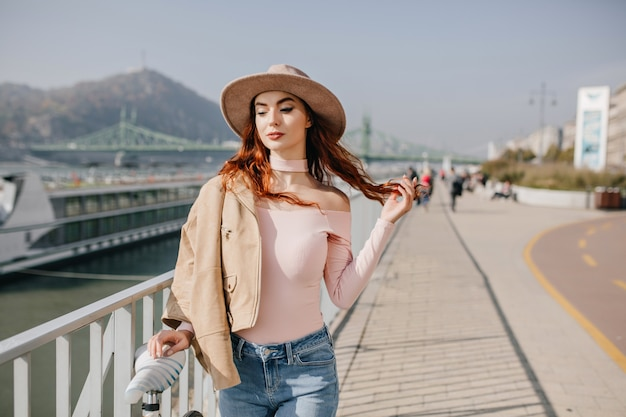 Jeune femme détendue joue avec les cheveux rouges sur les montagnes