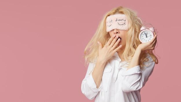 Jeune femme détendue en pyjama et masques de sommeil sur un mur rose. le réveil a réveillé la fille