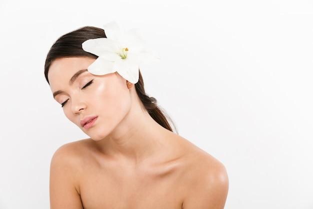 Jeune femme détendue avec les yeux fermés debout isolé avec fleur sur l'épaule