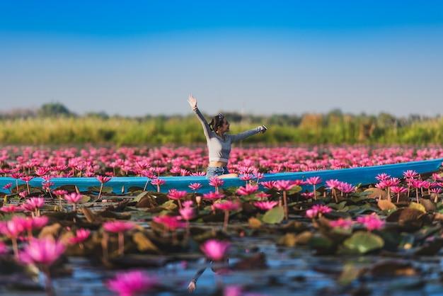 Jeune femme de détente avec beau champ de fleurs de lotus à la mer de lotus rouge