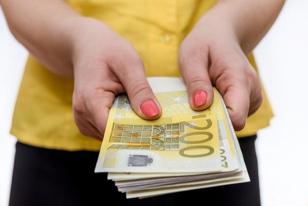 Jeune femme détient deux cents billets en euros dans ses mains