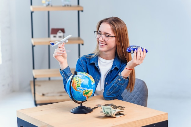 Une jeune femme détient un modèle d'avion et de voiture et choisit un meilleur moyen de transport pour voyager. concept de voyage et de vacances.