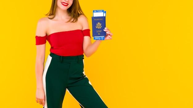 Une jeune femme détient un passeport et des billets d'avion. concentrez-vous sur une main avec des billets.