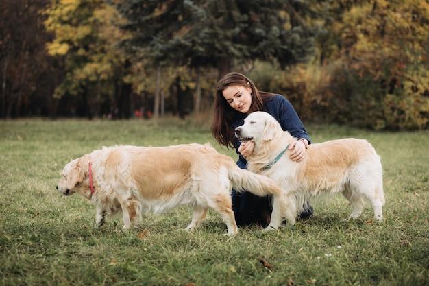Jeune femme avec deux golden retrievers dans un magnifique parc d'automne