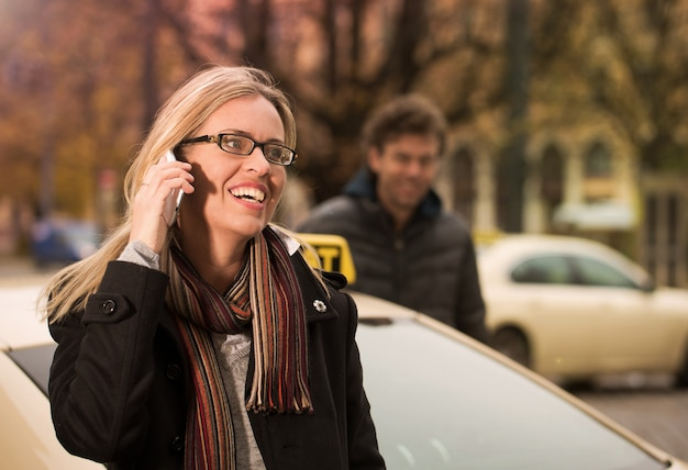 Jeune femme devant un taxi avec téléphone