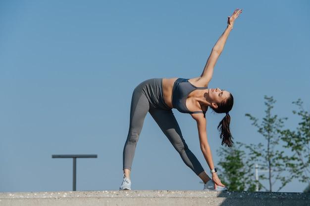 Jeune femme dévouée faisant de l'exercice à l'extérieur, se penchant en avant dans une torsion, touchant son pied. en haut gris et pantalon de yoga. par une journée ensoleillée sous un ciel bleu clair.