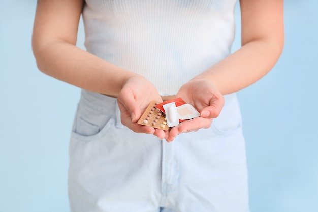 Jeune femme avec différents contraceptifs sur bleu