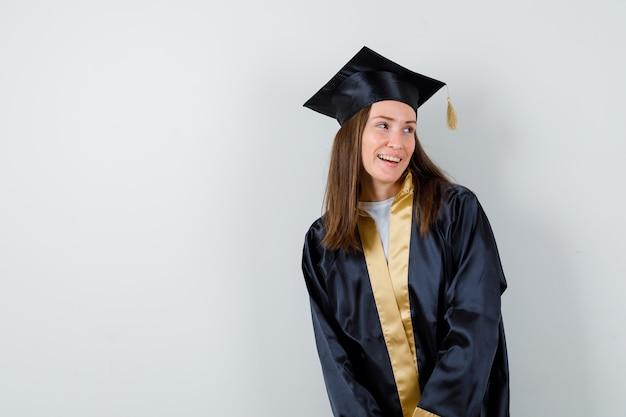 Jeune femme diplômée en détournant les yeux tout en posant en robe académique et à la joyeuse. vue de face.