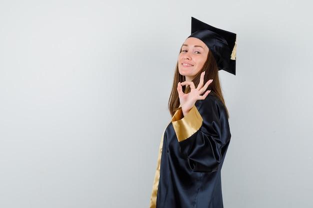Jeune femme diplômée montrant un geste correct en robe académique et à la vue positive, de face.