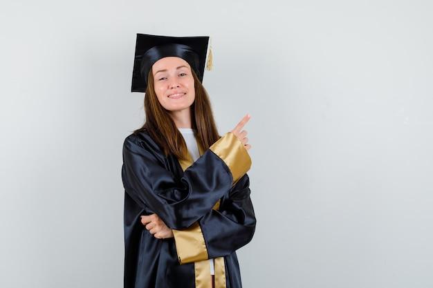 Jeune femme diplômée pointant vers le coin supérieur droit en tenue académique et à la vue de face, confiant.