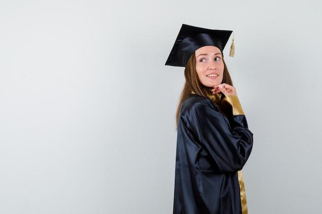 Jeune femme diplômée regardant par-dessus l'épaule en robe académique et à la recherche magnifique. vue de face.