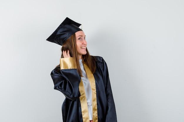 Jeune femme diplômée tenant la main sur les cheveux tout en posant en robe académique et à la recherche de cool. vue de face.