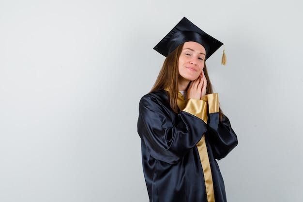 Jeune femme diplômée tenant la main sur la joue en robe académique et à la jolie. vue de face.