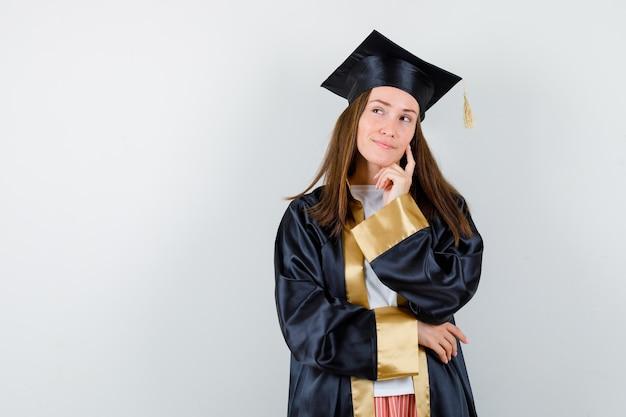Jeune femme diplômée en tenue académique debout dans la pensée pose et à la recherche pensive, vue de face.
